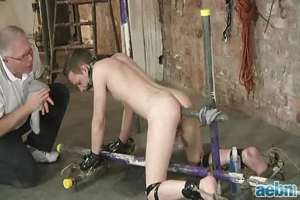 The master cuffs his slave and gives him some massive dildo punishment