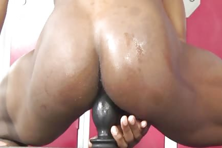 Bubble butt black guy sits on fat buttplug