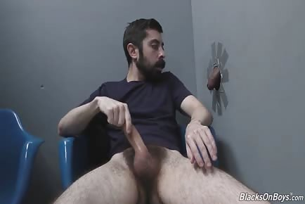 Bearded white dude blowing and fucking a black dong at a gloryhole